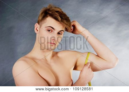 Young fitness man measuring his biceps.