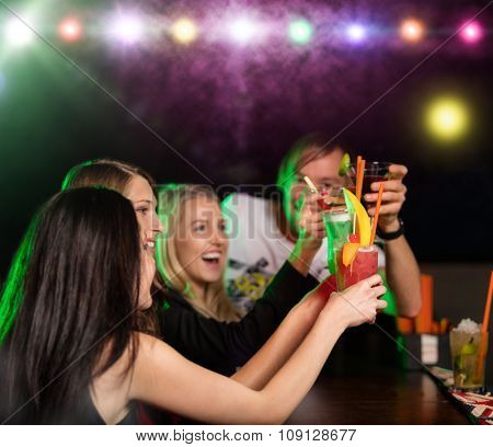 Young friends drinking cocktails together at night bar party
