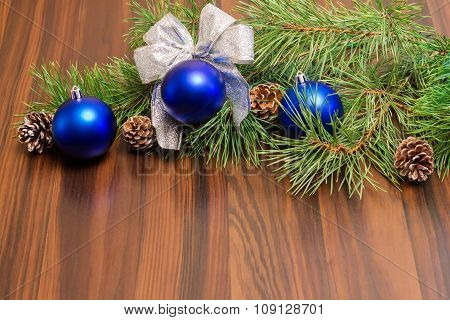Pine branches with cones and Christmas balls on a wooden backgro