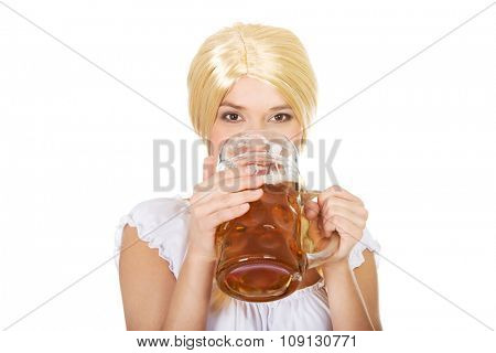 Young and beautiful bavarian woman drinking beer.