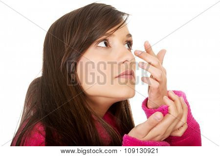 Woman in bathrobe putting contact lens in her eye.