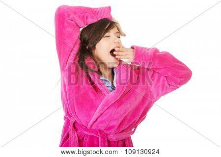 Beautiful stretching and yawning woman wearing pink bathrobe.