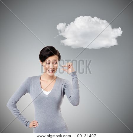 Mocking woman gestures small amount, isolated on grey background with cloud