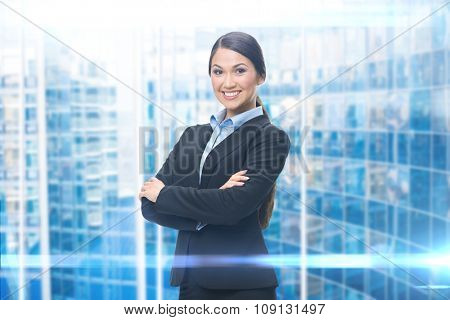 Portrait of business woman with hands crossed, blue background. Concept of leadership and success