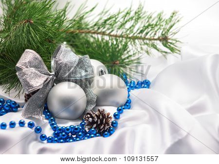 silver Christmas balls with bow with pine branches and blue bead