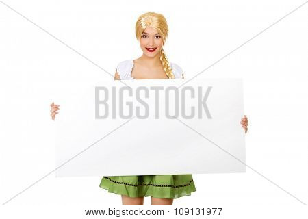 Woman wearing traditional Bavarian dress holding empty banner.