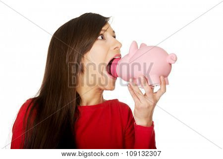 Student woman trying to eat a piggybank.