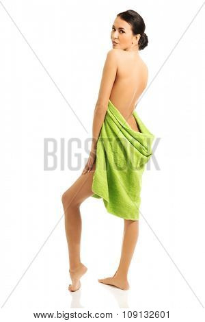 Full length back view woman wrapped in towel.