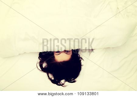 Scared woman hiding behind sheet in bed.