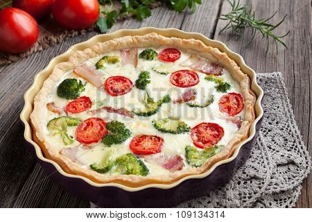 Traditional french homemade quiche lorraine tart pie recipe with broccoli, bacon, cheese and tomatoe