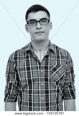 Blue toned black and white portrait of young man wearing glasses and checkered shirt