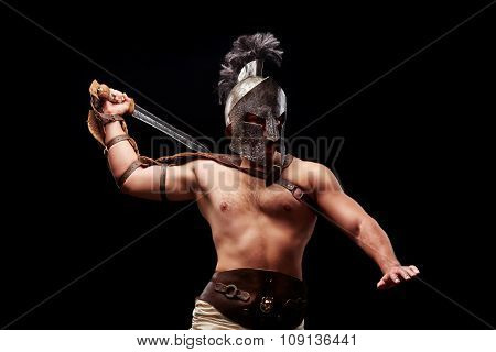 Gladiator with sword and armor on a black background