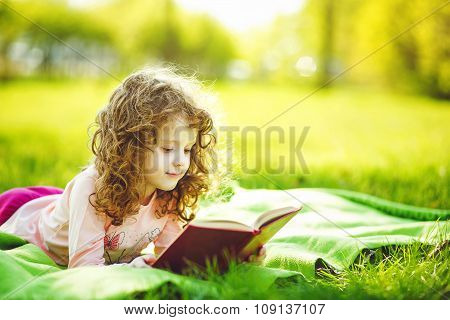 Little Girl Reading A Book In The Spring Park, Toning Photo.