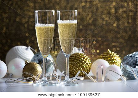 Two champagne glasses and christmas balls on the background
