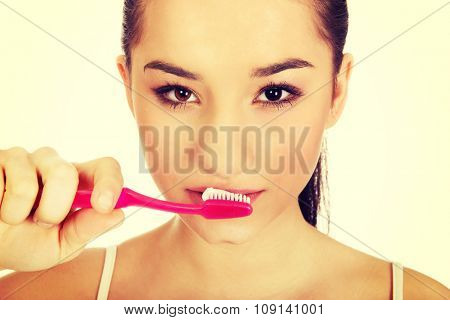 Young beautiful woman brushing her teeth.