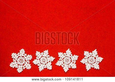 Four White Crochet Snowflakes In A Row