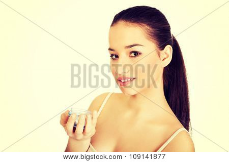 Happy young woman with cream moisturizer.