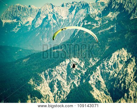 Paraglider Flying Over High And Rugged Range Of Alps Mountains