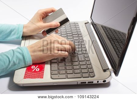 Woman Hand Holding A Credit Card And Typing. The Concept Of Cheap Shopping On The Internet.