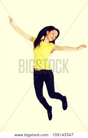 Young casual woman student jumping.