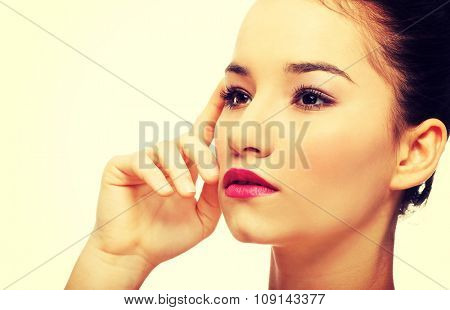 Beautiful woman with full make up touching face.