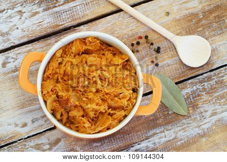 Polish bigos in saucepan on rustic wooden surface