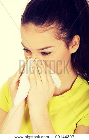 Teen woman with allergy or cold sneezing to tissue.