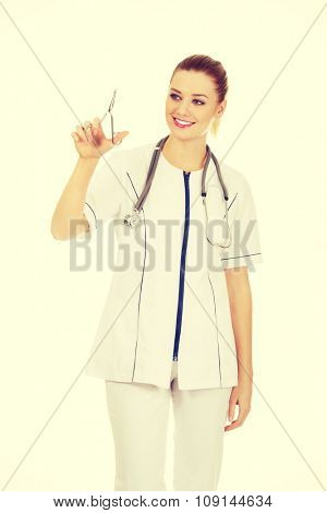 Happy female doctor with scissors in hand.