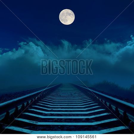 full moon in dark sky over railroad and clouds