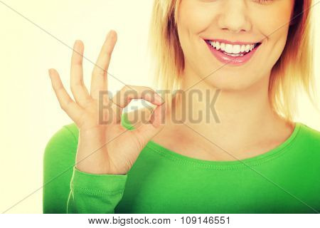 Casual young woman showing the perfect sign.