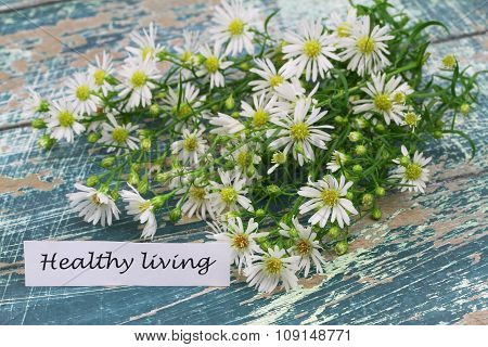 Healthy living card with chamomile flowers on rustic wooden surface