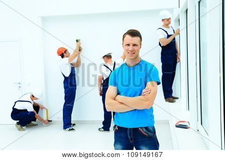 portrait of a smiling owner. against the backdrop of a team of builders