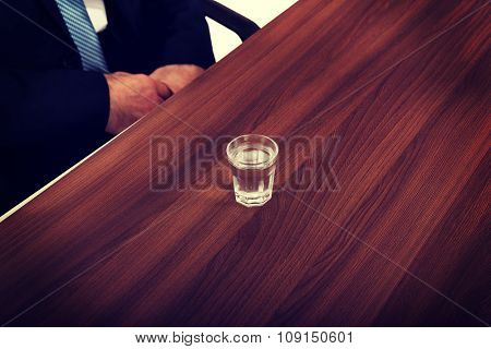 Glass of clear vodka on the desk in office.