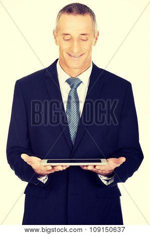 Smiling mature businessman using digital tablet.