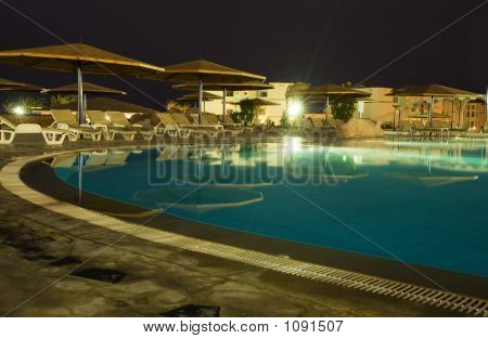Night Picture Of Rest. Swimming-Pool, Parasols And Sunbeds.