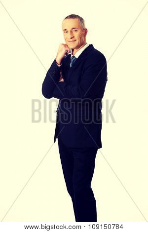Happy mature businessman with hand under chin.