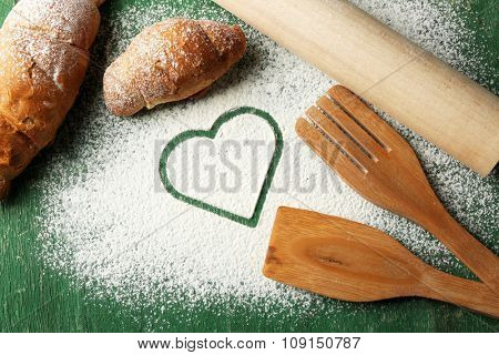 Hearts of flour and rolling pin on green background