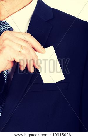 Mature businessman taking a blank card from pocket.