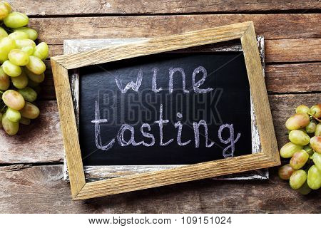 old chalk scripted frame with grape on wooden background