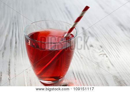 A glass of tasty garnet juice with a straw, on wooden background