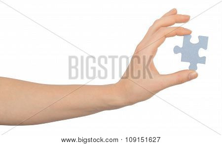 Womans hand holding puzzle piece