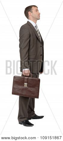 Man in suit with suitcase, side view