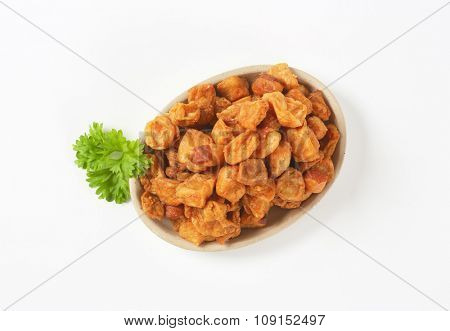 plate of salty pork greaves on white background