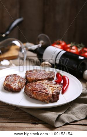 Roasted beef fillet on plate, on wooden background