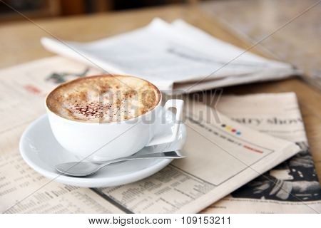 Cup of tasty cappuccino and newspapers on table