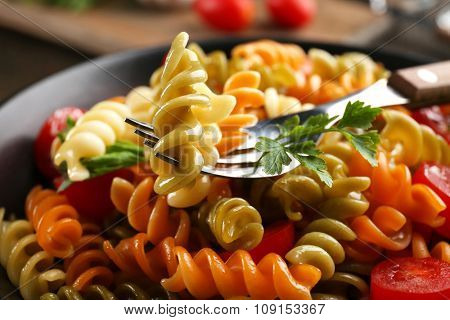 Delicious macaroni dish in black bowl on served wooden table, close up
