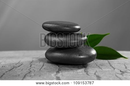 Pile of pebbles with leaf on the table against grey background