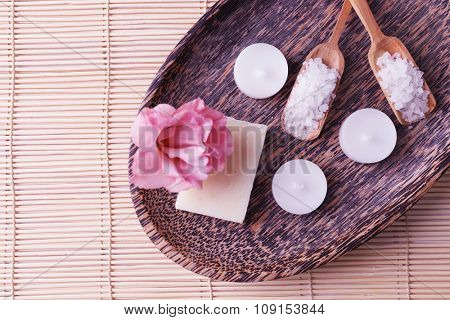 Spa composition of candles, soap, sea salt and flower on bamboo background