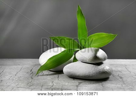 Composition of pebbles with leaf on the table against grey background