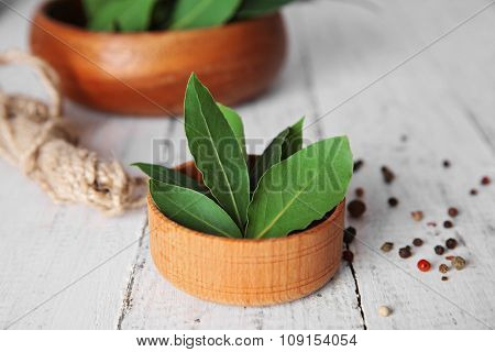 Fresh bay leaves in bowl on white wooden table